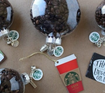 Clear Ornaments Filled With Coffee Beans And Starbucks Tags Stating, Thanks This One Is On Me