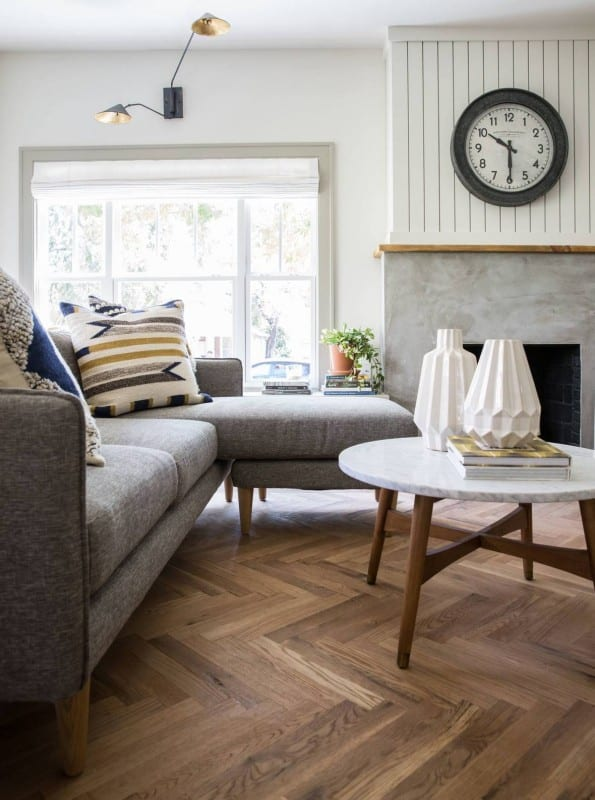 Fixer Upper Giraffe House Living Room Wooden Floor, White Wall, Marble Fireplace, Grey Couch