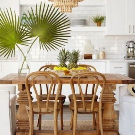 White Kitchen With Wooden Table And Tropical Plants