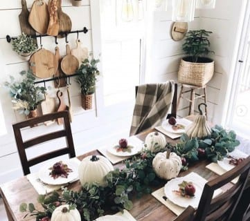 Wood Dining Table With Fall Tablescape; Greenery, White Pumpkins, And Apples On Each Plate