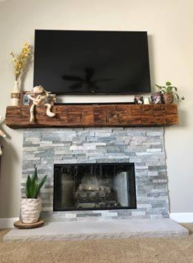 Grey Brick Fireplace Topped With A Rustic Wood Shelf