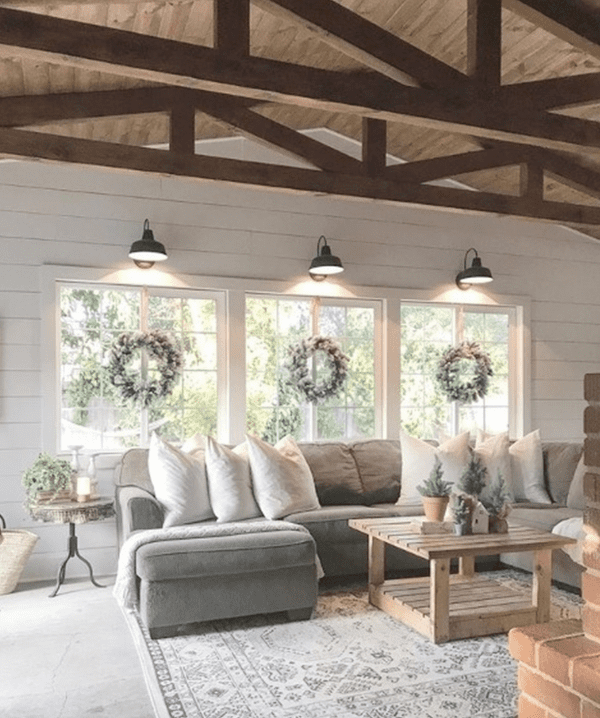 Living Room With High Rise Ceilings And Wooden Beams And Open Windows With Lights Above And Wreaths And Grey Couch With White Cushions