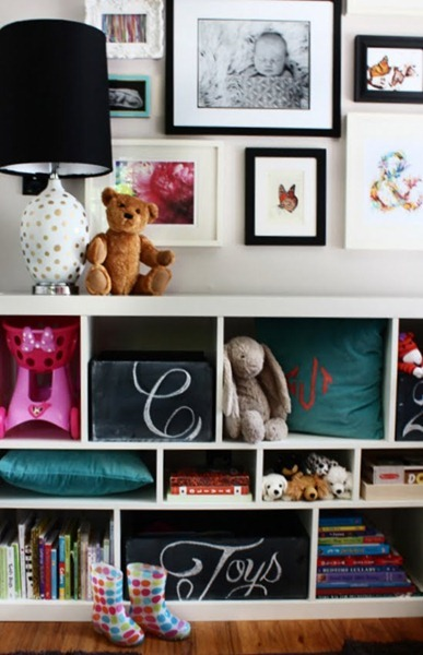 Toy Room Shelves With Chalkboard Toy Box Storage And Colorful Books, Pillows, Toys, Pictures On Wall And Rainboots