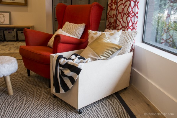 Plywood Storage Box With Wheels Filled With Pillows And Blankets Next To Arm Chair And Window