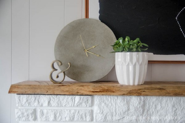 Simple DIY Concrete Clock With Gold Hands Sitting On Wooden Shelf Above White Brick Mantle And White Planter With Greenery