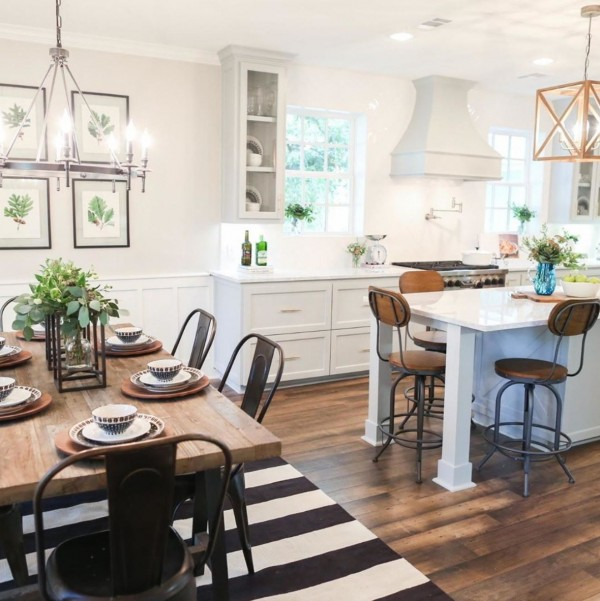 White Kitchen With Wooden Floor And Table And Metal Accents