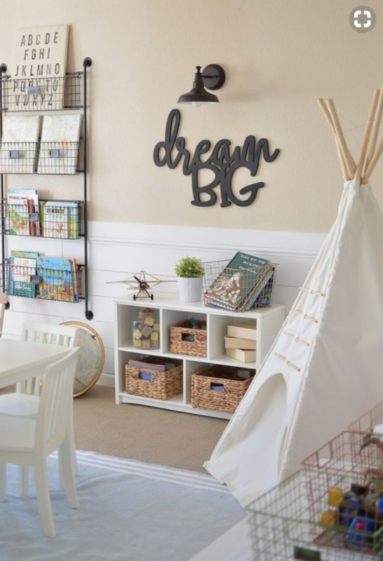 Play Room With Hanging Metal Baskets Full Od Books, White Bookshelf With Baskets And Blocks, And A Teepee And White Table