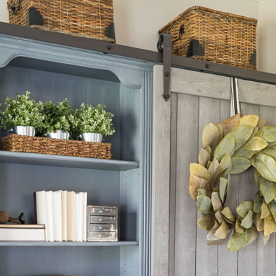 Sliding Door Bookcase With Leaf Wreath And Blue Shelves
