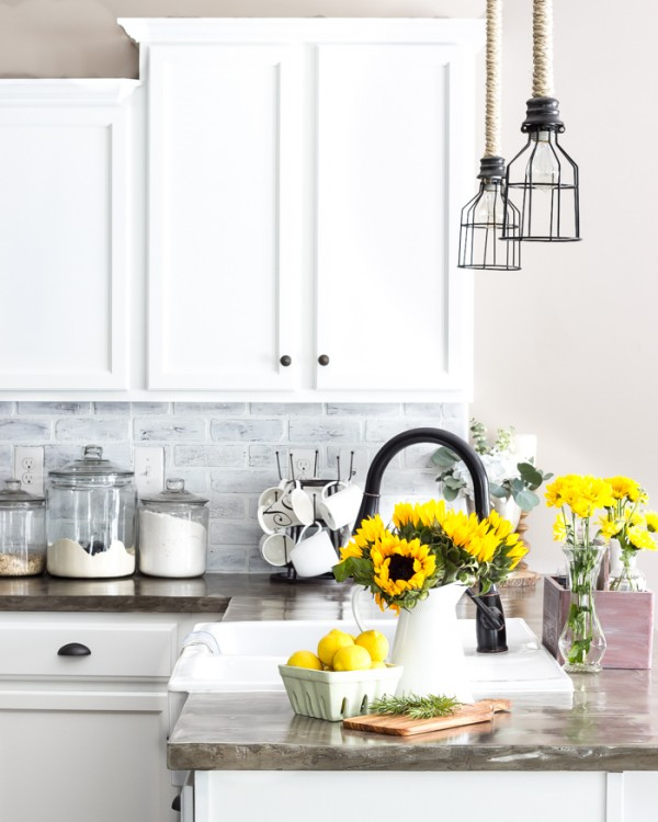Stunning Light Kitchen With White Cabinets And Grey Brick Backsplash And Glass Jars And Sunflowers, And Lemons