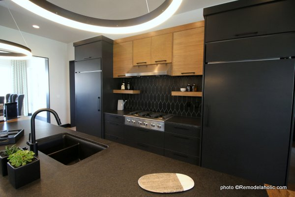 Modern Dark Gray Kitchen Cabinets With Light Wood Upper Cabinets, Black Tile Backsplash, UVPH House 27 Emerald Homes