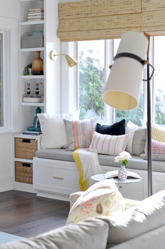 White And Grey Window Bench With Colorful Pillows And Wicker Baskets