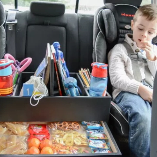 Child In Car Seat With Center Seat Holding A DIY Backseat Car Organizer With Treats, Drinks, Books, And Activities