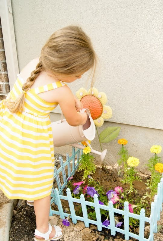 Gardening With Kids, Little Girl In Yellow And White Striped Sun Dress Watering A Flower Garden