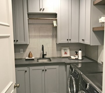 Laundry Room With Grey Cabinets, Tile, Washer And Dryer
