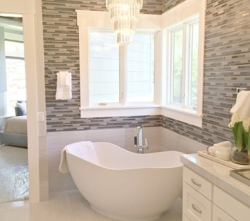 White And Grey Bathroom With Chandelier And Tiled Wall