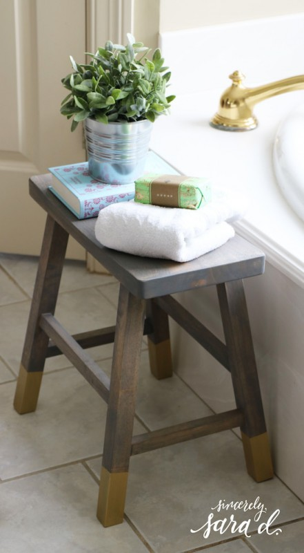 Wooden Bathroom Stool With Gold Accents Next To Tub With Book, Towel And Soap On Top