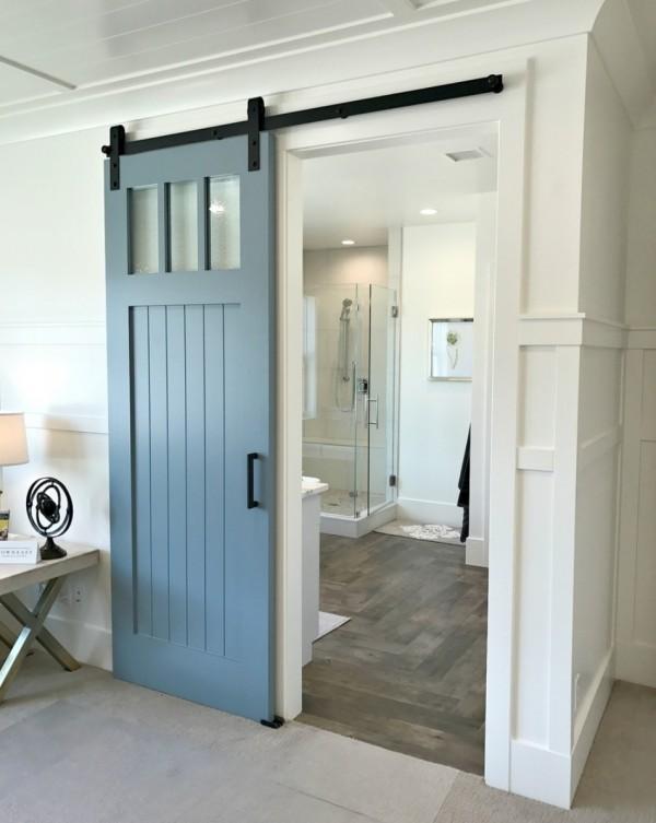 Blue Barn Door Leading Into Bathroom, White Walls, Black Handles
