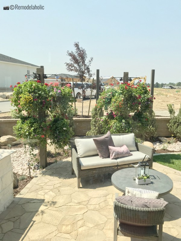 Patio area in the garden with a loveseat. SLPH 2018 Home 5 Regal Homes, Photo by Remodelaholic