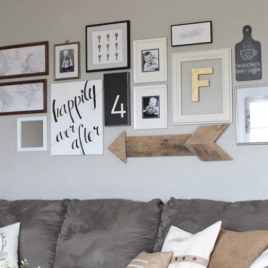 Gallery Wall Above Grey Couch With Wooden Arrow And White Frames With Black Accent