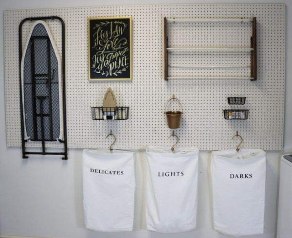 Laundry Room Pegboard With Hanging Laundry Bags Labeled Delicates, Lights, And Darks Ironing Board Also Hanging