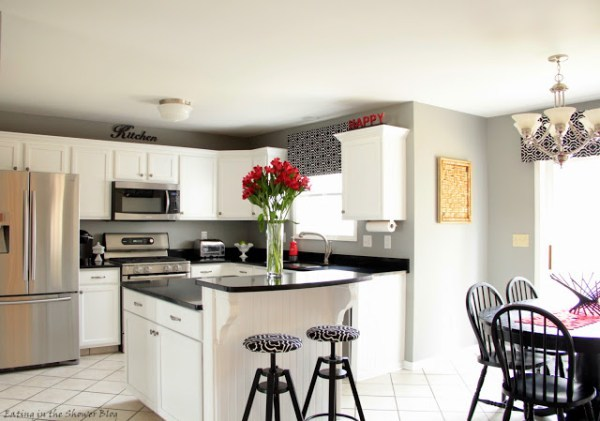 Black And White Kithen With White Cupboards And Black Countertops And Wallpaper