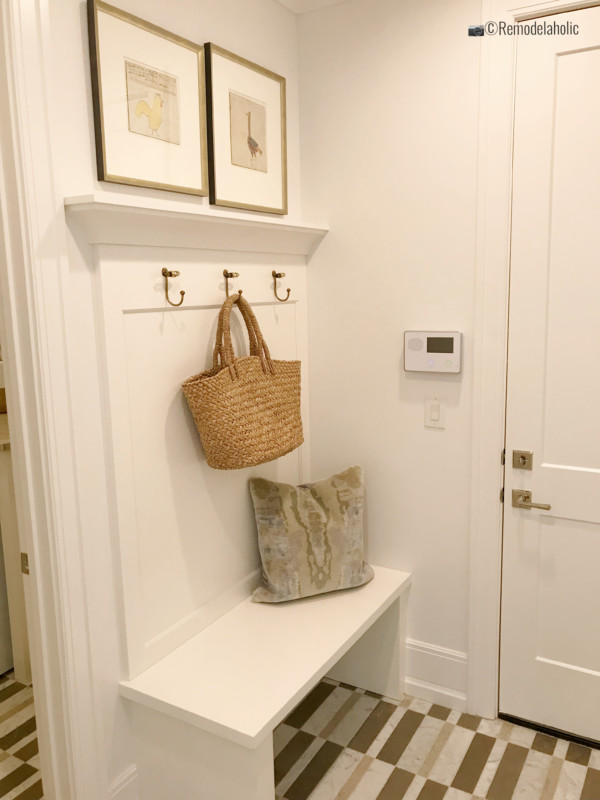 Simple white build in mudroom bench with hooks. SLPH 2018 Home 4 Ivory Homes, Photo by Remodelaholic.com