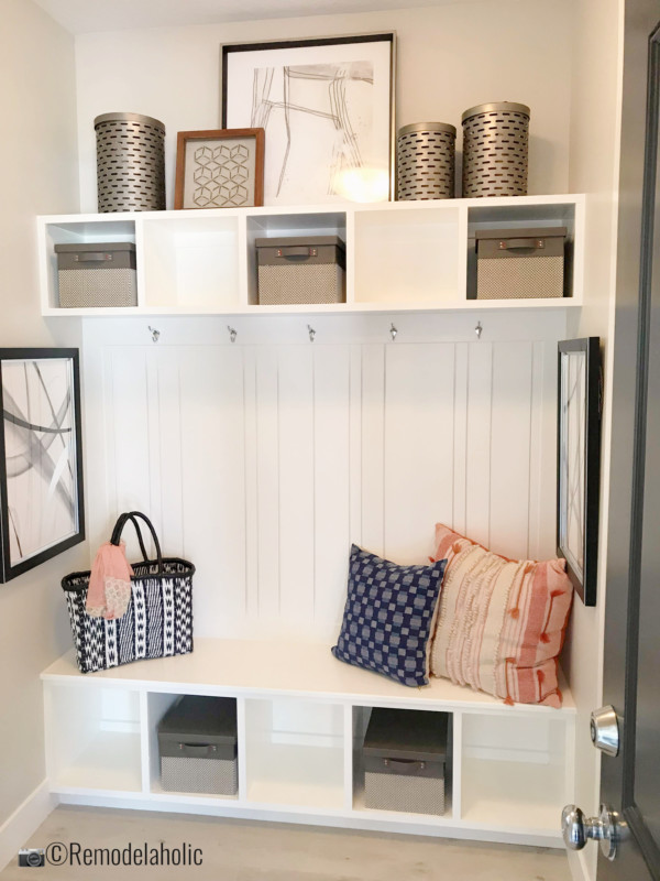 Adding artwork and pillows to a mudroom bench. UVPH 2018 Home 11 Concord Homes, Tailored Interior Design, Photo by Remodelaholic