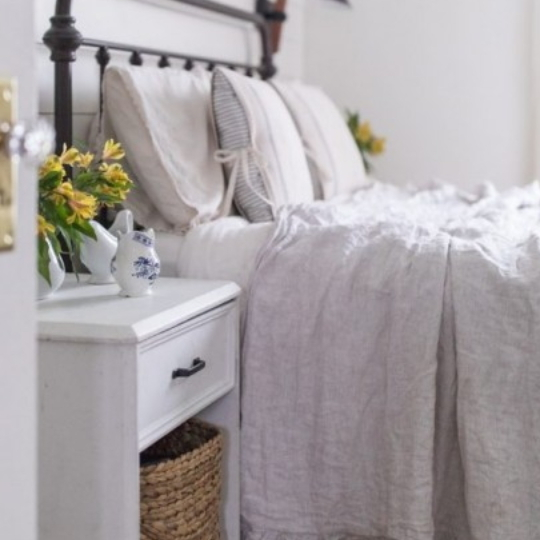 White And Grey Bedroom Inspiration With White Nigtstand, Wicker Basket And Yellow Flowers