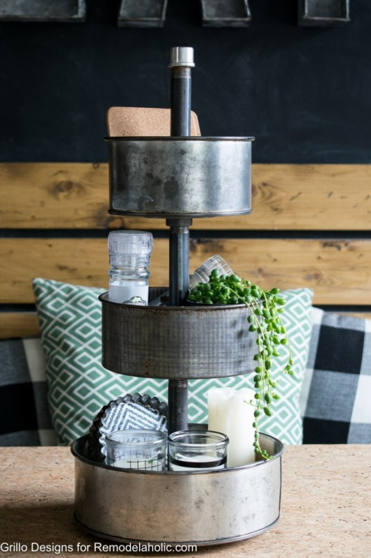 Rotating Three Tier Metal Tray Organizer On Wood Table With Salt, Candles, And Green Plant Inside