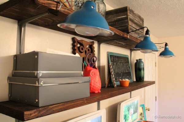 Wood Wall Shelves With Metal Brackets And Blue Light Fixtures