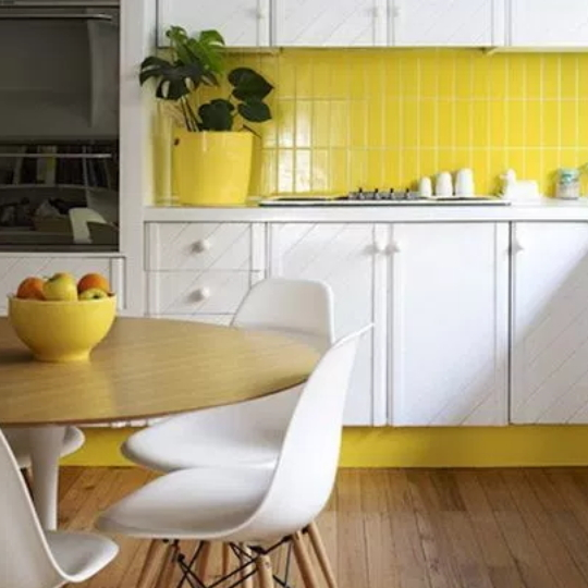Kitchen With Yellow Walls And Trim, White Cupboards And Chairs, Wooden Table And Flooring