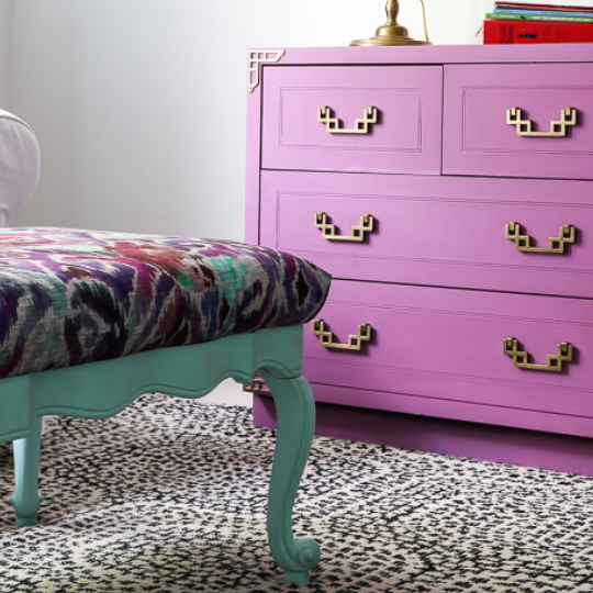 Coffee Table Upcycled To A Upholstered Bench, Colorful Paint, Bench Has Green Legs, Dresser In Background Has Purple Paint And Gold Handles