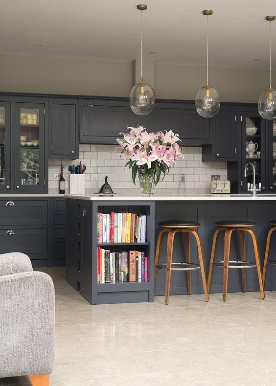 Dark Kitchen Caniets With Glass Light Fixtures And Wood Barstools