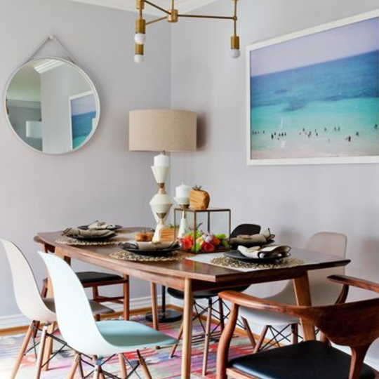 Dining Areaa With Wood Table, Circle Mirror, And Blue Painting