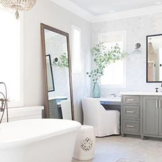 Farmhouse Bathroom With White Tub, Colored Cabinets, Leaning Wall Mirror