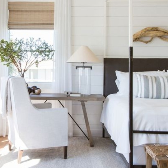 Farmhouse Bedroom With White Walls, White Bedding, White Chair, Accents Of Brown