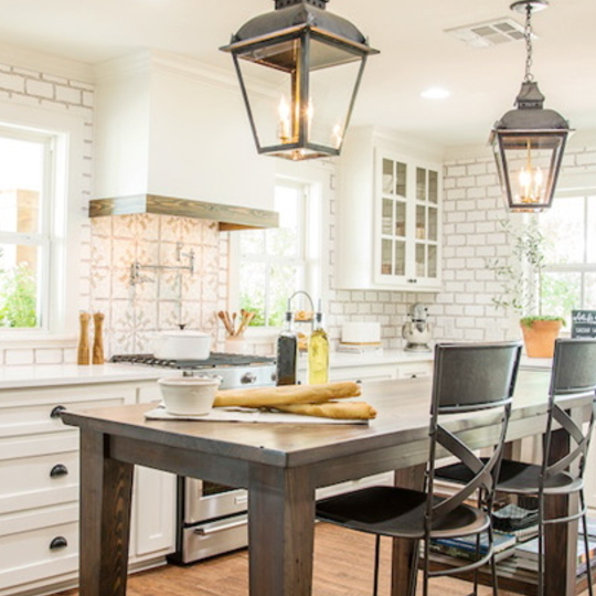 Fixer Upper Worm House Kitchen With Wood Table And White Brick Walls, White Cabinets And White Vent Hood