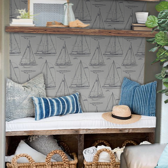 Nautical Room With Uholstered Sitting Bench, Wicker Baskets Underneat, Blue And Grey Pillows With Sail Boat Wallpaper
