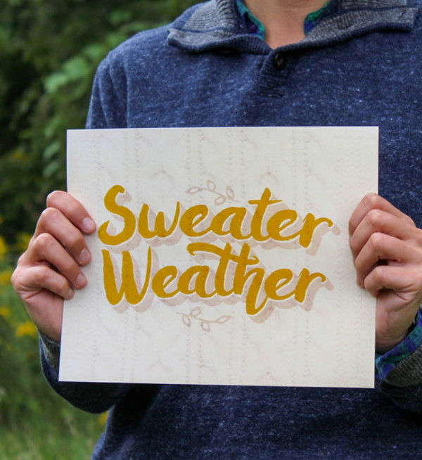 Sweater Weather Printable With Yellow Font Being Held By Someone With Blue Sweater On
