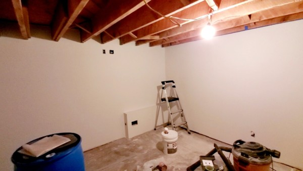 basement remodel - white painted walls with open ceiling beam joists