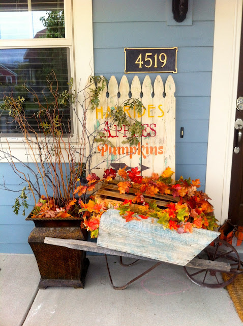 Cute Fall Porch With Wheelbarrow Full Of Fall Leaves And Fence With Fall Words
