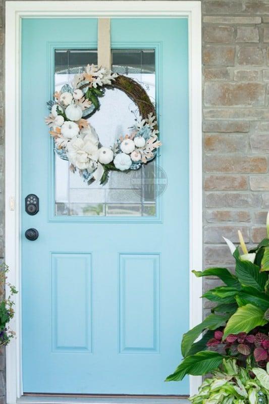 Porte bleue de coquille d'oeuf avec la citrouille blanche, la couronne florale bleue et orange