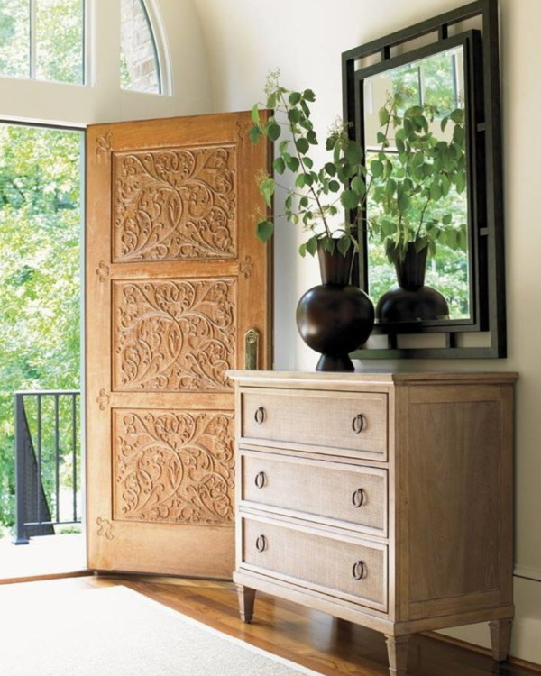 Entryway With Wooden Detailed Front Door, Wood Dresser, Black Mirror, Vase And Greenery