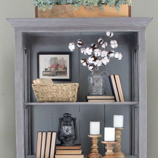 Grey Cabinet With Wood Accents, Books, White Candles And Basket