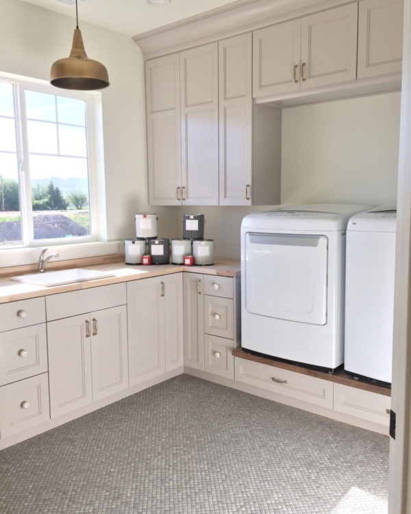Laundry Room With Raised Washer And Dryer And Built In Cabinets