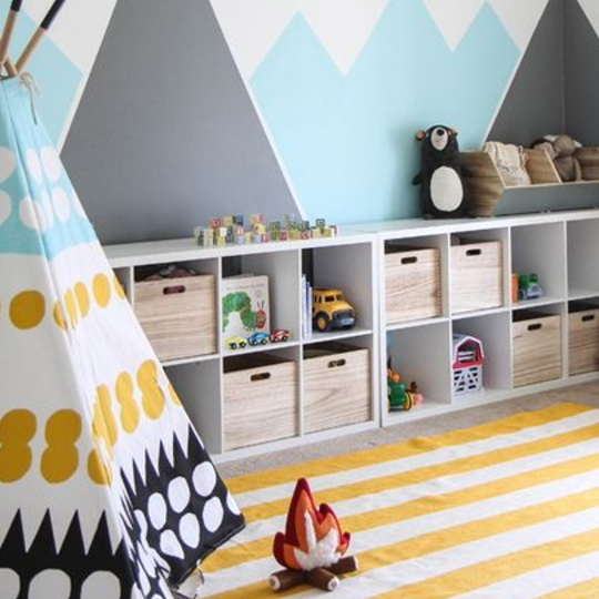 Playroom With Striped Yellow Rug, Colorfull TeePee And Square Cubbies With Mountains On Wall