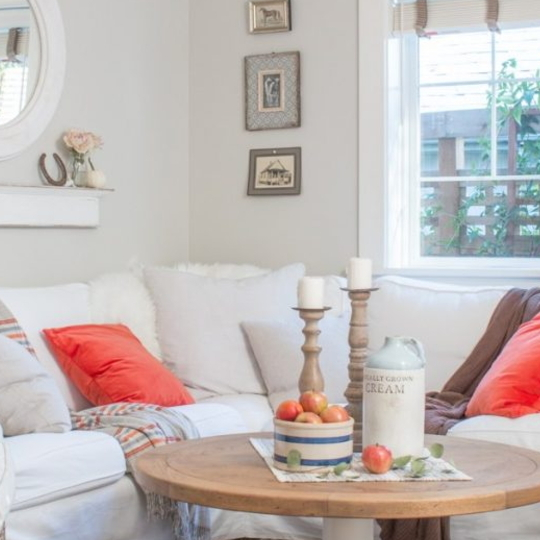 White And Grey Room With Wood Circle Table And Wood Candlesticks And Red Accents