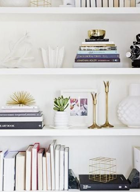 White Bookshelves With Books, Gold Accent Decor And White Vases