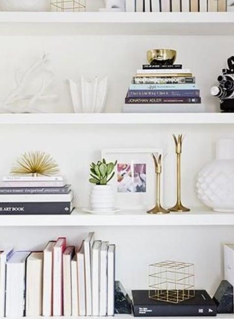 White Bookshelves With Books, Gold Accent Decor And White Vases