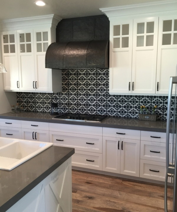 White Cupboards, Black Handles, Black And White Tiled Backplash And Metal Stove Hood